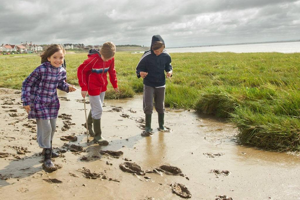 Family at a mud dipping event at RSPB Ribble Discovery Centre