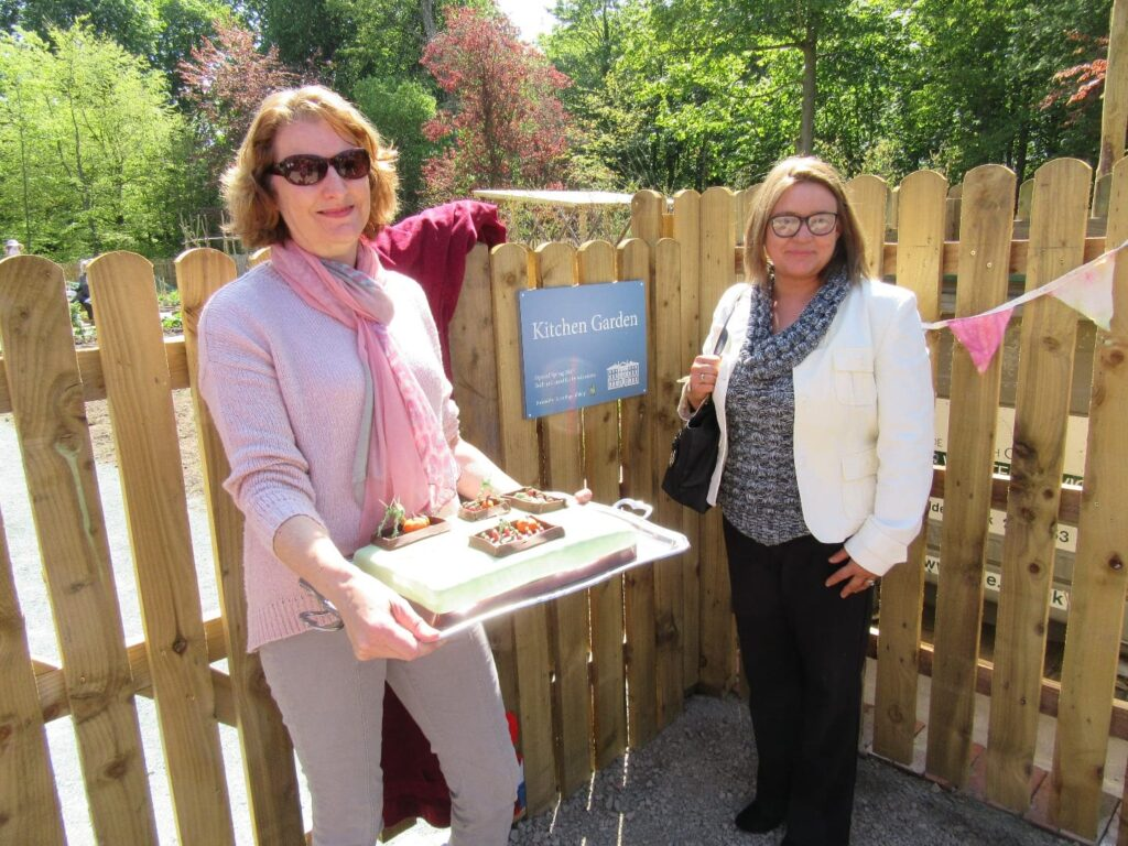 Opening of the new Kitchen Garden at Lytham Hall. Sue Lowe (volunteer coordinator) and Emma Barrett (Tesco) in front of kitchen garden sign, with celebratory cake